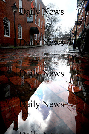 Newburyport: Buildings, lamposts, and breaking clouds are reflected in a puddle caused by sporatic rain Friday. Jim Vaiknoras/Staff photo