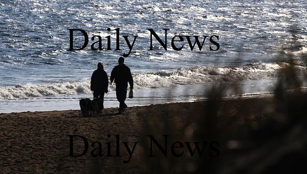 Newbury: A couple walk their dogs along Plum Island Beach early Sunday morning. Jim Vaiknoras/Staff photo