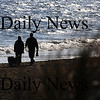 Newbury: A couple walk their dogs along Plum Island Beach early Sunday morning. Jim Vaiknoras/Staff photo