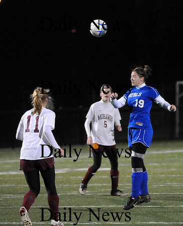 Quincy: Emma Cannon (19) heads the ball away from a Millis defender during Tuesday night's Eastern Mass. State Final game in Quincy. Photo by Ben Laing/Staff Photo