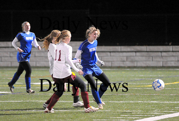 Quincy: Emilly Bitchell (21) passes the ball away from two Millis defenders during Tuesday night's Eastern Mass. State Final game in Quincy. Photo by Ben Laing/Staff Photo