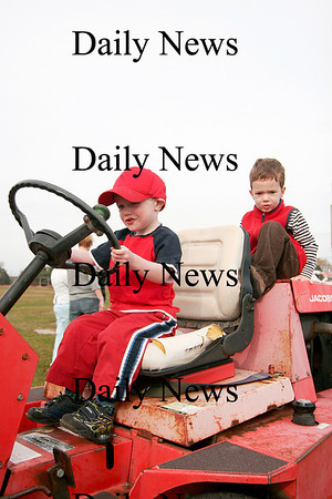 """Newbury: Dalton Cronin, 4, left, and Will Pflaum, 3, both of Newburyport, play on a tractor at the Plum Island Airport Tuesday morning. The two boys were part of the Spencer-Pierce-Little Farm's """"Farm Friends"""" program, which visited the airfield. Photo by Ben Laing/Staff Photo"""