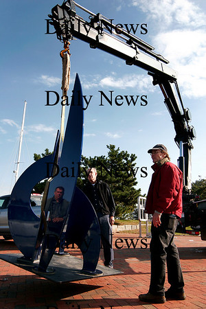 """Newburyport: Curator Jay Havighurst, right, directs as sculptor Gilbert Boro, center, watches as his latest work, """"Buckingham Blue,"""" is lowered by crane for installation in the seventh Somerby's Landing Sculpture Park show on Newburyport's waterfront. Photo by Ben Laing/Staff Photo"""