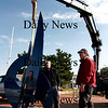 "Newburyport: Curator Jay Havighurst, right, directs as sculptor Gilbert Boro, center, watches as his latest work, ""Buckingham Blue,"" is lowered by crane for installation in the seventh Somerby's Landing Sculpture Park show on Newburyport's waterfront. Photo by Ben Laing/Staff Photo"