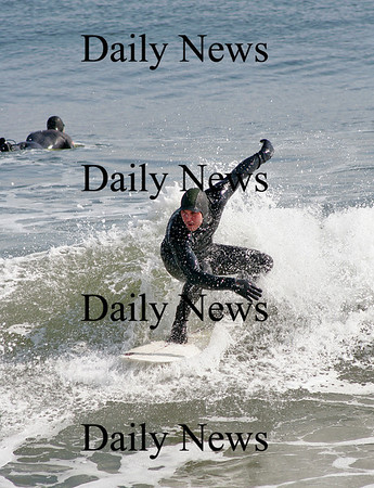 Newbury: A surfer catches a wave Tuesday morning at Plum Island. Photo by Ben Laing/Staff Photo