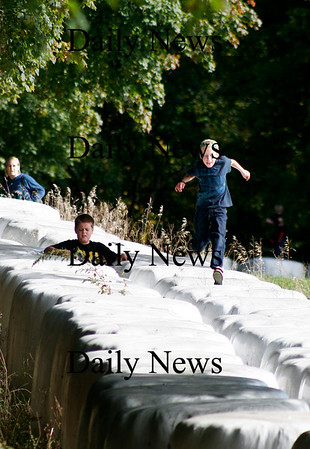 Newbury: Gavin Carmichael, 10, of Amesbury, runs atop the hay bales near Old Town Hill in Newbury with his friend, Cooper Willingham of Newburyport. Photo by Ben Laing/Staff Photo