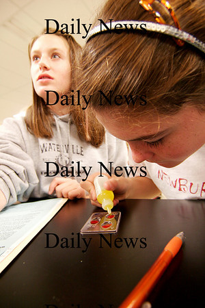 Newburyport: Seventh grader Meghan Stanton, right, and her partner, Peyton Bailey, add chemicals to simulated blood during an experiment for a Crime Scene Investigation program at the Middle School in Newburyport Tuesday morning. Photo by Ben Laing/Staff Photo