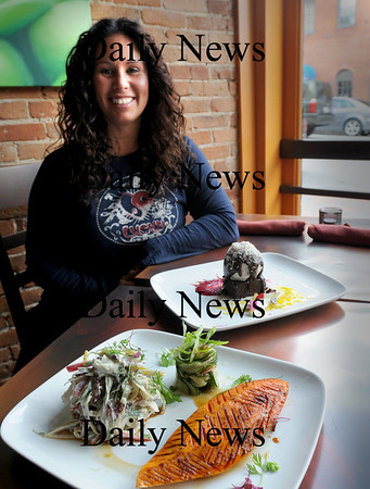"Newburyport: Grezzo owner Alissa Cohen with samples of raw foods in her new restaurant on State Street in Newburyport. In front is handcarved papaya ""steak"" crusted with star anise served horseradish vermicelli. In back is a rich brownie sundae  with housemade gelatto with chocolate truffle and Brazil nut crumble. Bryan Eaton/Staff Photo"