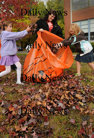 Salisbury: Boys and Girls Club counselor Hannah Warren holds a pumpkin bag while Haylee Clogston, 8, left, and Gillian Sweeney, 9, among others fill them with leaves. The filled bags will used for decoration at Sunday's Fall Hayride and Halloween Hayride at Lion's Park. Bryan Eaton/Staff Photo