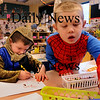 Newbury: Kindergartner Mason Martinello, 5, right, dressed as Spiderman grabs a marker, as he and Cameron Murray, 6, dressed as a knight, work on spooky photos for their Halloween party at Newbury Elementary School on Thursday afternoon. Bryan Eaton/Staff Photo