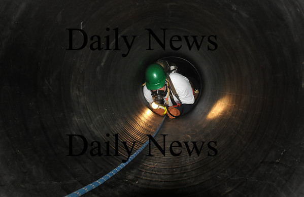 """Newburyport: Beverly firefighter Brad Saunders inches his way in a dark tunnel to help rescue a """"victim"""" trapped and unconscious. Area firefighters attended a rescue workshop for people trapped in tunnels, or shafts behind the Newburyport Fire Department. Bryan Eaton/Staff Photo"""