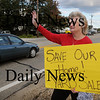 Salisbury: Ralston family friend Gloria Marks holds a sign as traffic on Route 110 in Salisbury drives by letting them know about the yard sale. Bryan Eaton/Staff Photo