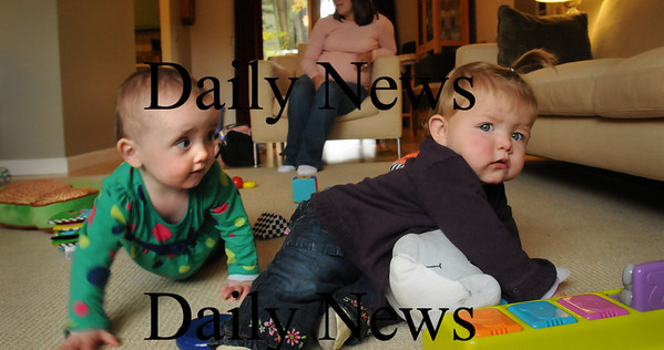 Newburyport: Lilah Thompson, 14 months, left, makes friends with Catherine Conway, 1, at a Newburyport Mother's Club get together. Bryan Eaton/Staff Photo
