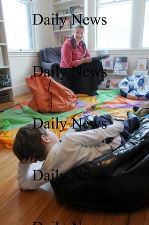 Librarian Beth Sceery reads in the Children's Room of the Emma Andrews Branch Library earlier this year, which is now closed to lead paint being found on the premises. File Photo/Newburyport Daily News