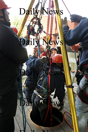 """Newburyport: Fire and rescue personnel pull Boston firefighter Neal Mullane from a shaft during rescue training on Thursday afternoon. Sent in as a rescuer of someone trapped in the shaft, he had to be """"rescued"""" as well, his breathing apparatus """"failed."""" Bryan Eaton/Staff Photo"""