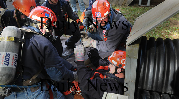 """Newburyport: Area firefighters pull the """"victim"""", Salisbury call firefighter John Cutter, from the end of a tunnel behind the Newburyport Fire Station. They were learning rescue techniques for people who may be trapped in tunnels or shafts. Bryan Eaton/Staff Photo"""