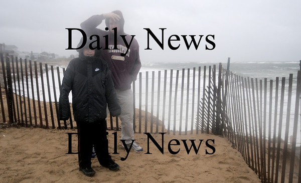 Newbury:Michael Bennett of Newburyport and his son Nicholas, 10 came out Sunday to see teh high surf on Plum Island. Jim Vaiknoras/Staff photo