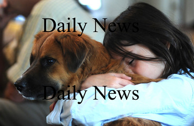 Newbury: Emma Gimbrere hugs her dog Pearl at the Blessing of the Animals at the First Parish Church in Newbury Sunday morning. Jim Vaiknoras/Staff photo