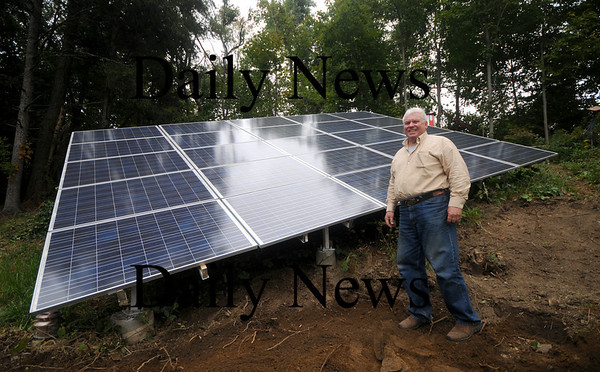West Newbury: Dennis Unger stands with a solar array in his West Newbury Yard. His home will be on the  Green Buildings Open House Tour  Saturday. JIm Vaiknoras/Staff photo