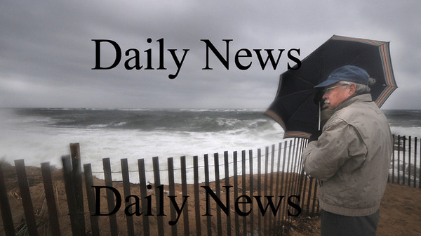 Newbury: Carl Demikat of Newbury braces himself against the wind as he checks out the high surf on Plum Island. Demikat doesn't like the rain , but was convinced to come out and watch the storm by him wife Marilyn Jordan. Jim Vaiknoras/Staff photo