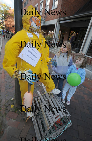 Newburyport: Rebecca and Kaitlyn Adams look over their entry in the scarecrow contest at the annual Newburyport Harvest Festival Sunday in Market Square.Their sister Emma also help them out. Jim Vaiknoras/Staff photo