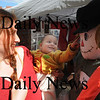 Newburyport: Julianna Goldstone and her son Wilcca look at the Daily News entry in the scarecrow contest  at the annual Newburyport Harvest Festival Sunday in Market Square.Their sister Emma also help them out. Jim Vaiknoras/Staff photo