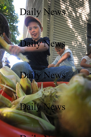Newbury: Brendan Muldowney and Mile Shea husk corn at the annual Harvest Festival at the Spencer-Pierce Little Farm in Newbury. Jim Vaiknoras/Staff photo