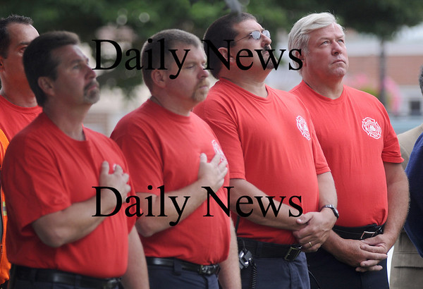 Newburyport: Newburyport firefighters Paul Gouldthorp, Paul DuBois, John Piretti and Lt. John Kelleher watch as Newburyport Veteran Agent Kevin Hunt raises the Flag of Honor, an American flag containing the names of the victims of the attacks on 9/11/01, at Brown Square Friday morning.