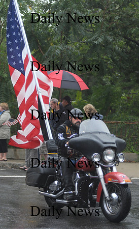 Newburyport:A member of the Patriot Guard carries a large American Flag in  the motorcade for the funeral of Sgt. Jordan Shay as it makes it's way down Summer Street in Newburyport Saturday morning. Jim Vaiknoras/Staff photo