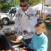 Newburyport: Stephen Pfingst of David's Tavern and his daughter Madilyn 7, prepares brushetta with roasted eggplant using ingredients from the Heron Pond Farm at the Farm to Table Tour at the Newburyport Farmers Market Sunday. Jim Vaiknoras/Staff photo