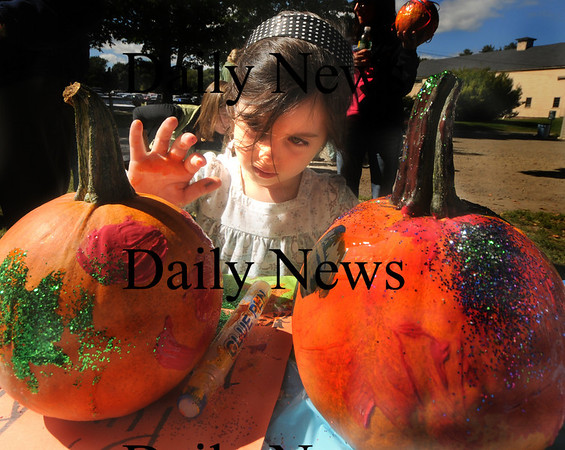 Newbury: Carly Webb, 4, of Newburyport, put some finishing touches on her pumpkin at the annual Harvest Festival at the Spencer-Pierce Little Farm in Newbury. Jim Vaiknoras/Staff photo