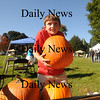 Rowley: Lee Dalzell, 8, lefts a very heavy pumpkin at the farmer market on Rowley Common Sunday morning. Jim Vaiknoras/Staff photo