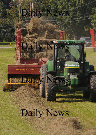 Amesbury: A worker from Kimball Farm in Haverhill bails hay at the Woodsom Farm in Amesbury Monday afternoon. Jim Vaiknoras/Staff photo