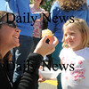 Amesbury: Nicole O'Callaghan offers her daughter Meg, 3, a piece of corn bread at the 5th annual Amesbury Firefighter Chili Cook off in the Barking Dog parking lot Sunday. Jim Vaiknoras/Staff photo
