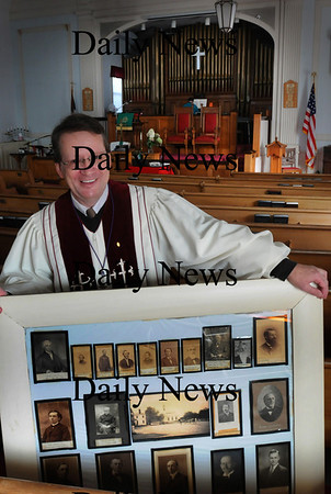 Salisbury: Reverend Rusty Davis with photos of his predecessors of the late 18th and early 19th centuries which hang in the East Parish Meetinghouse which has hosted the Methodist denomination since the building was constructed in 1834. Davis is the 82nd pastor that has served the East Parish of Salisbury, which was Congregationalist before the Methodists filled the spot. Bryan Eaton/Staff Photo Newburyport News   Thursday September 17, 2009.