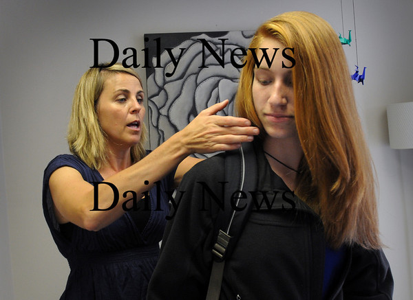Newburyport: Dr. Donovan shows Bianca Hagan, 15, of Amesbury how to distribute weight into a backpack, the correct tension on the straps. Bryan Eaton/Staff Photo  Newburyport News Thursday September 24, 2009.