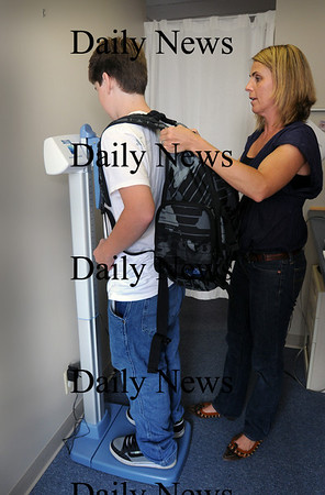 Newburyport: Dr. Jeaniene Donovan weighs Justin Hagan, 14, of Amesbury with and without his backpack. Bryan Eaton/Staff Photo  Newburyport News Thursday September 24, 2009.