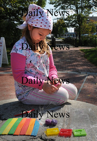 Amesbury: Katelynne Casali, 7, spends some time in the sun Monday making clay sculptures while visiting Amesbury's Upper Millyard with her mother Annie. Bryan Eaton/Staff Photo