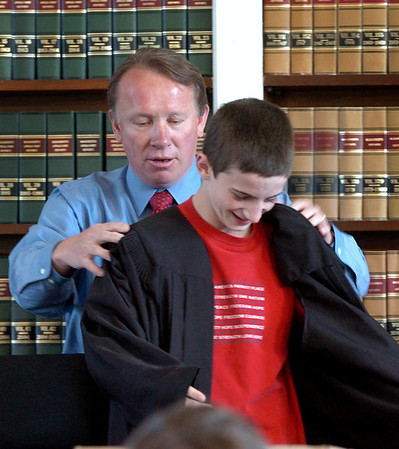 "Newburyport: Newburyport Superior Court Judge Richard Welch puts his robe on Nock Middle School eighth-grader Chris Orlando at the beginning of a mock trial yesterday morning. The eighth-graders at the Newburyport school have been reading to ""Kill a Mockingbird"" in their language arts class with several students taking on characters in the famous novel in the mock trial. Bryan Eaton/Staff Photo"