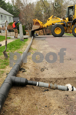 Amesbury: A bulldozer dumps crushed stone over temporary water pipes to make it easier for people to go into their driveways. The water main along Route 150 in Amesbury from Route 110 to the town park area, and a few side streets, is being replaced. Bryan Eaton/Staff Photo