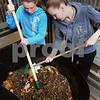 Newburyport: Liz Fiascone, left, and Sam Wahlgren, both 15, turn the green and brown matter in a compost bin at Newburyport High School. Bryan Eaton/Staff Photo