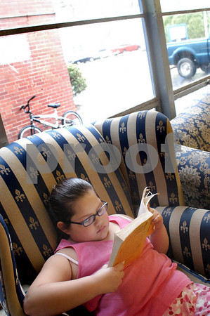 "Salisbury: With the rain falling Tuesday afternoon, Abbrielle Carrera, 8, of Salisbury snuggles up with the book ""Ozman of Oz"" in the reading room at Boys and Girls Club. Bryan Eaton/Staff Photo"