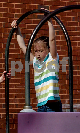 Åmesbury: Melissa Skan, 9, of Amesbury uses her strength to pull herself up on some playground equipment at Amesbury Elementary School on Wednesday. She was in the Recreation Department's Afterschool Program where all activities were outside on the 80 degree plus day. Bryan Eaton/Staff Photo