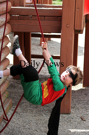 Amesbury: Oscar Nevers, 4, of Amesbury, scales the side of the playground at Amesbury Town Park Monday morning, dressed as Batman's sidekick, Robin. Photo by Ben Laing/Staff Photo
