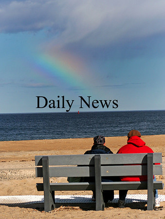Salisbury: A couple sits on a bench at the Salisbury Beach Reservation Monday afternoon, as a rainbow appeared over the Atlantic. Photo by Ben Laing/Staff Photo