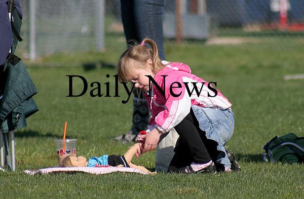 Byfield: Megan Freiermuth, 5, of Merrimac, ignores the lacrosse game between Pentucket and Triton to focus on her doll while on the sidelines at Tuesday's game. Photo by Ben Laing/Staff Photo