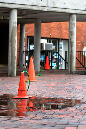 Newburyport: A hose snakes its way out of a basement shop on Inn Street in Newburyport, pumping water from the latest rain storm into a drain. Photo by Ben Laing/Staff Photo