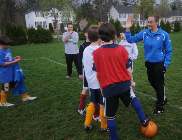 Newburyport: Claire Zimmeck of the Boston Breakers high fives some of the Newburyport Youth Soccer u12  players during a clinic she gave to the boys at Cherry Hill in Newburyport Thursday night. Jim Vaiknoras/Staff photo