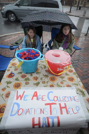 Newburyport: Olivia Gracey 11, and her sister Abby, 12, stay dry as they collect donation to help Haiti Sunday morning on the corner of Liberty Street and State Street. The pair are hoping to continue collecting this upcoming week. Jim Vaiknoras/Staff photo