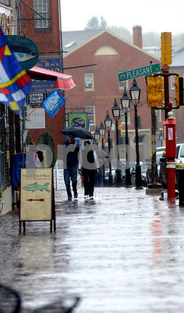 Newburyport:A couple share an umbrella as they make their way up State Street in Newburyport during the rain and snow Friday afternoon. Jim Vaiknoras/Staff photo